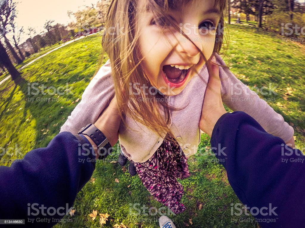 Father Swinging Daughter Around under Her Arms stock photo