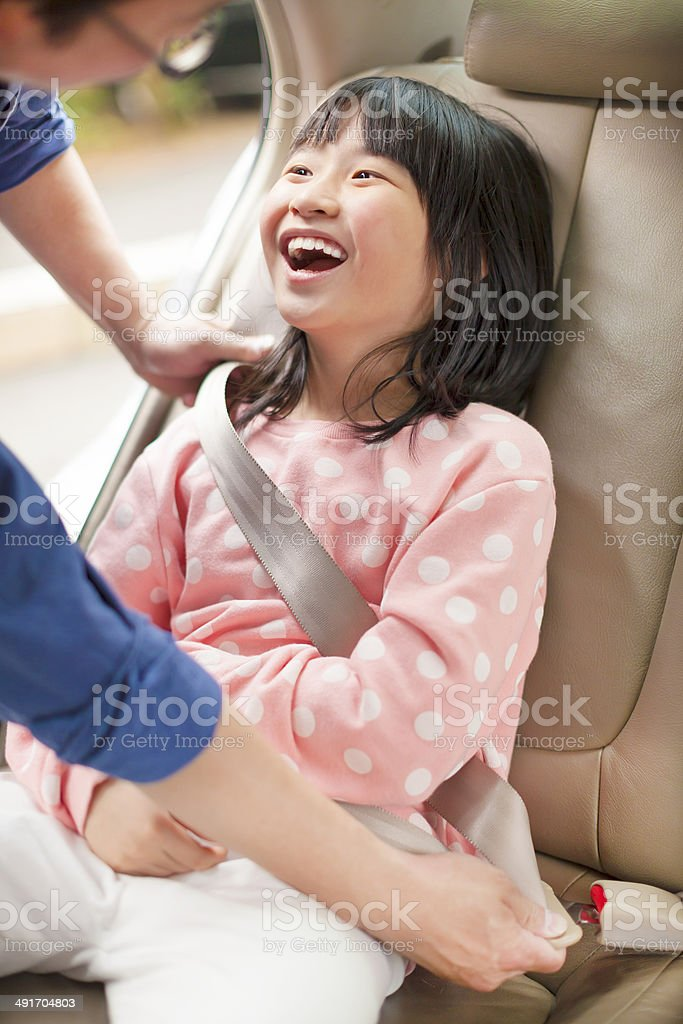 father take care daughter to fasten a seat belt stock photo
