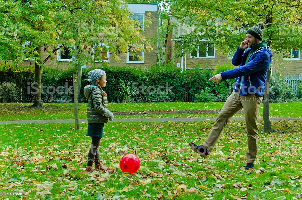 Father Talking On The Phone Playing Ball With His Daughter. stock photo