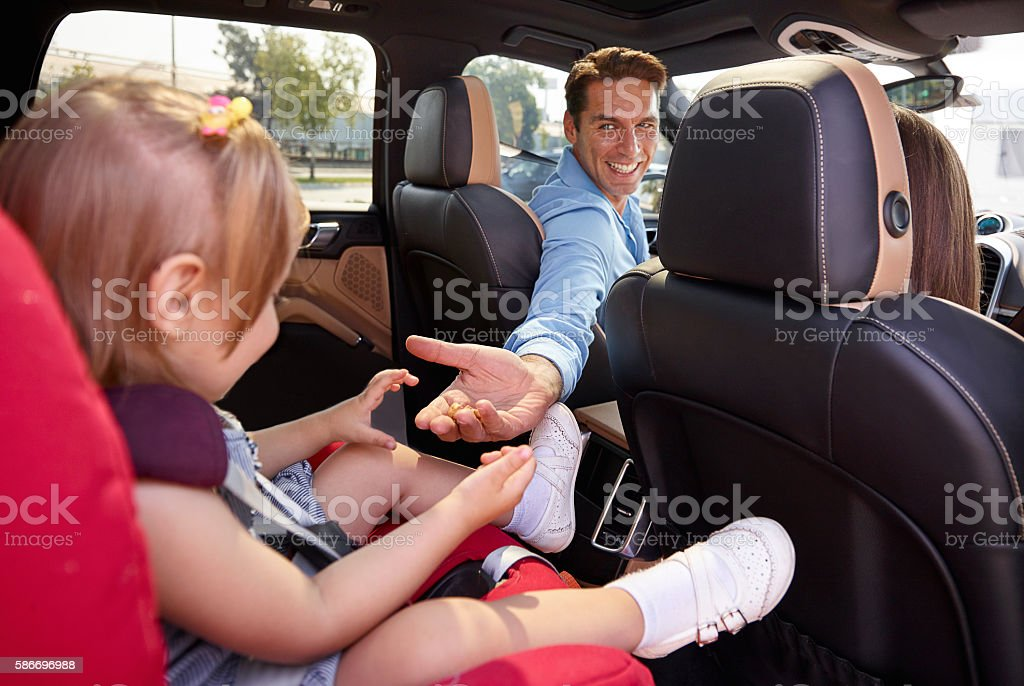 Father talking with his daughter in car seat stock photo