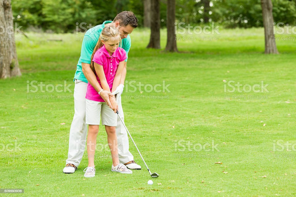 Father teaches daughter how to golf stock photo