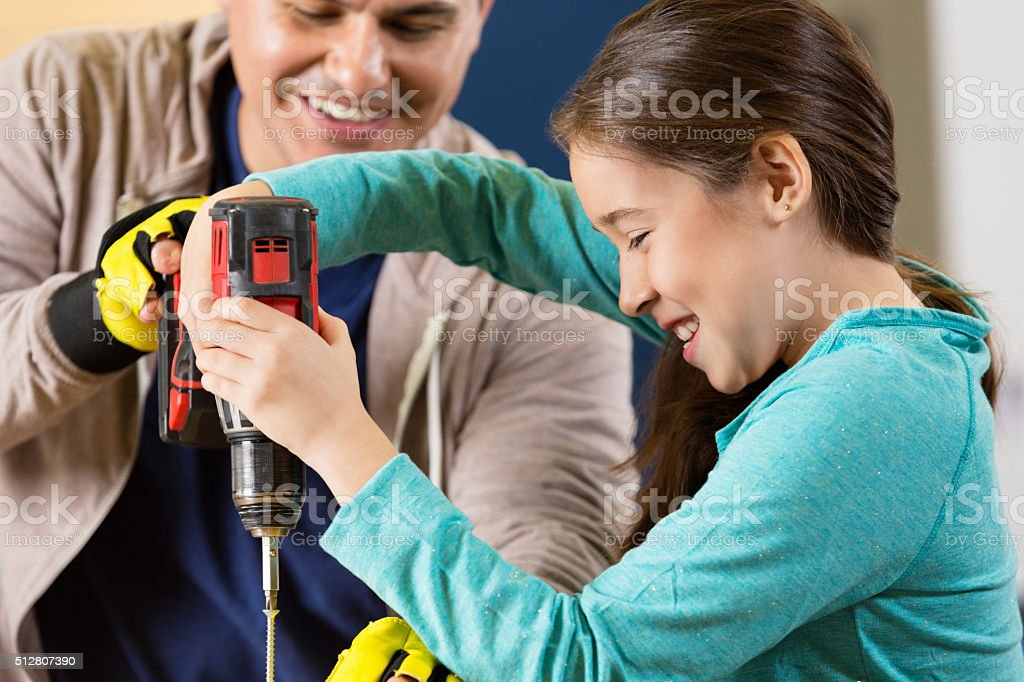 Father teaches daughter how to use power drill stock photo