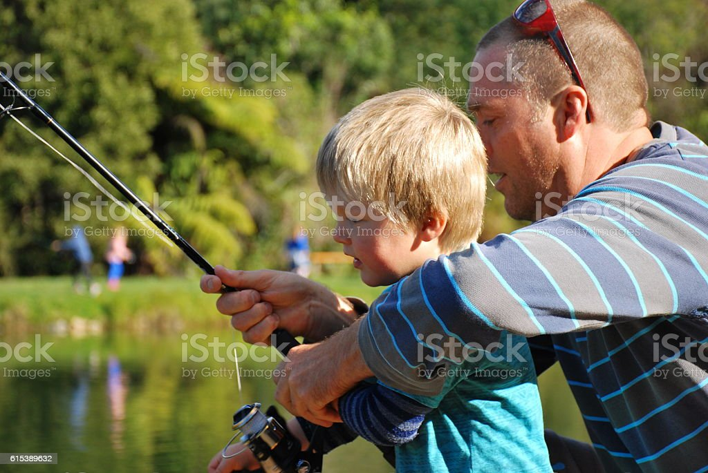 Father Teaches his Young Child how to Fish stock photo