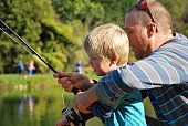Father Teaches his Young Child how to Fish