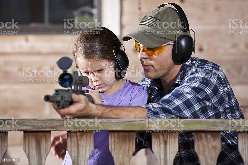 Father teaching child to handle gun stock photo