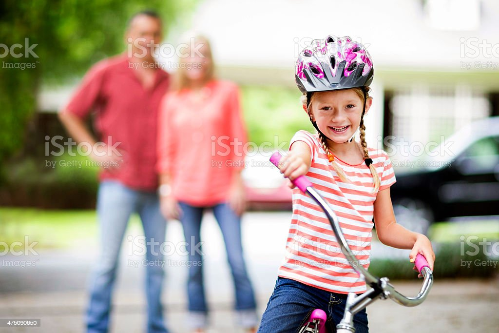 Father teaching daughter how to ride a bike. stock photo