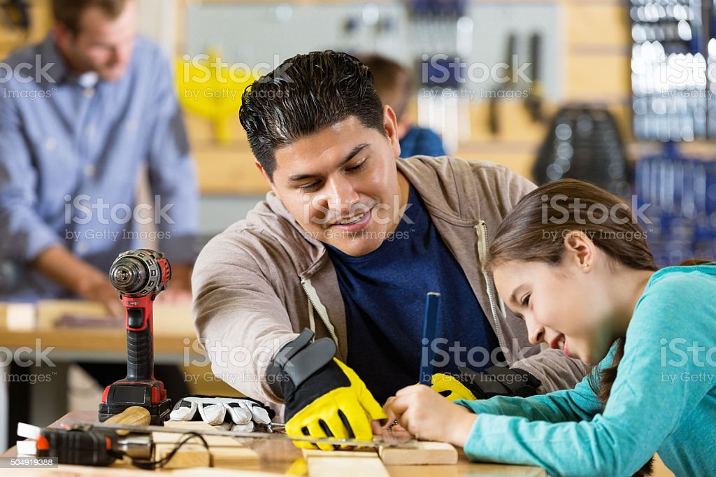 Father teaching daughter to measure boards in workshop or garage stock photo