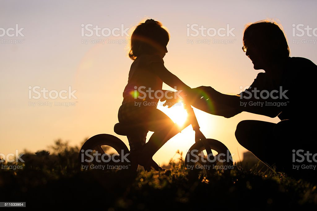 father teaching daughter to ride bike at sunset stock photo