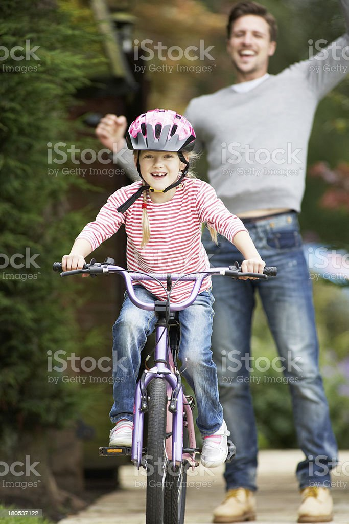 Father Teaching Daughter To Ride Bike In Garden stock photo