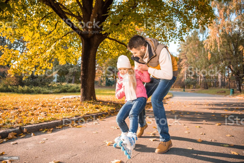 Happy father teaching little daughter to roller skating in autumn park