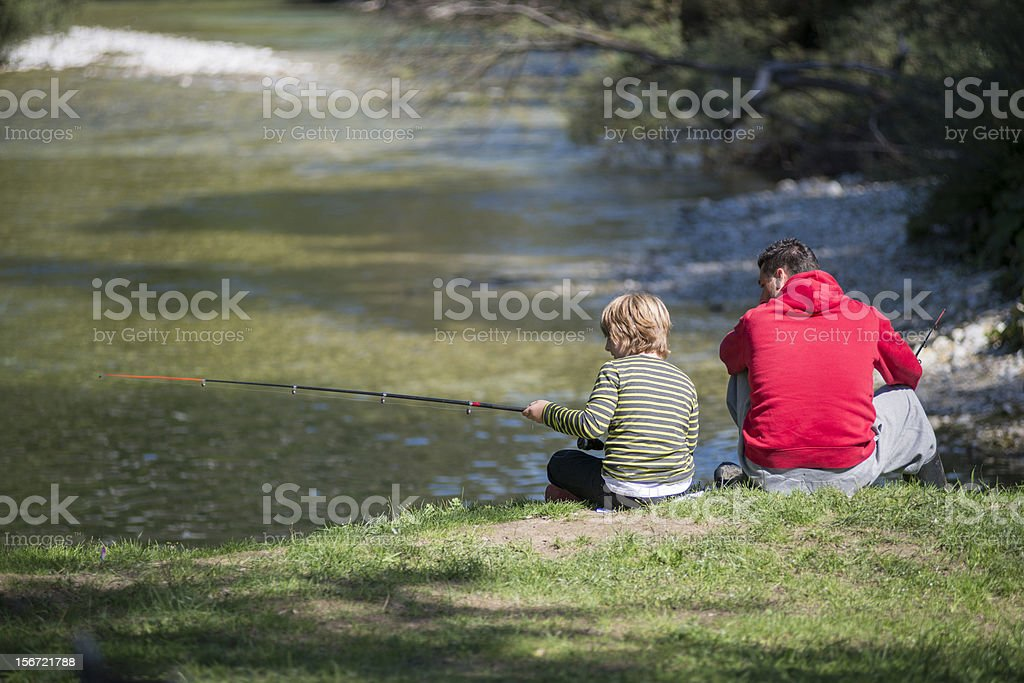 Father teaching his son how to fish on a river royalty-free stock photo