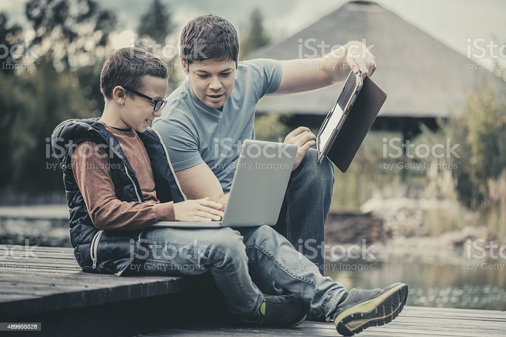 Father teaching his son how to use tablet and laptop stock photo