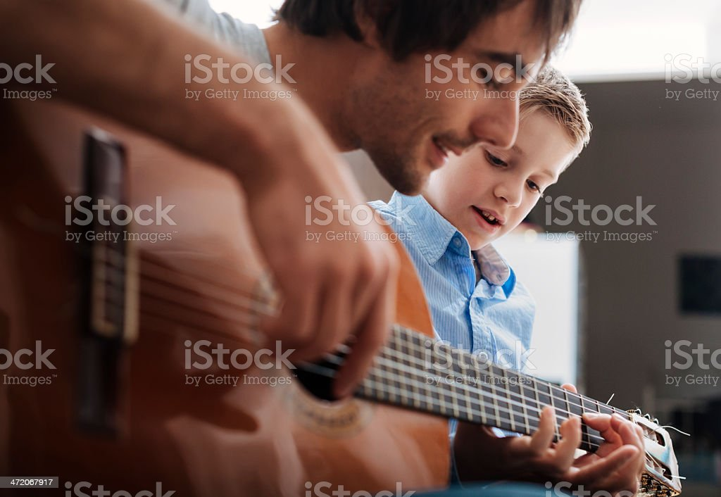 Father teaching son Guitar stock photo