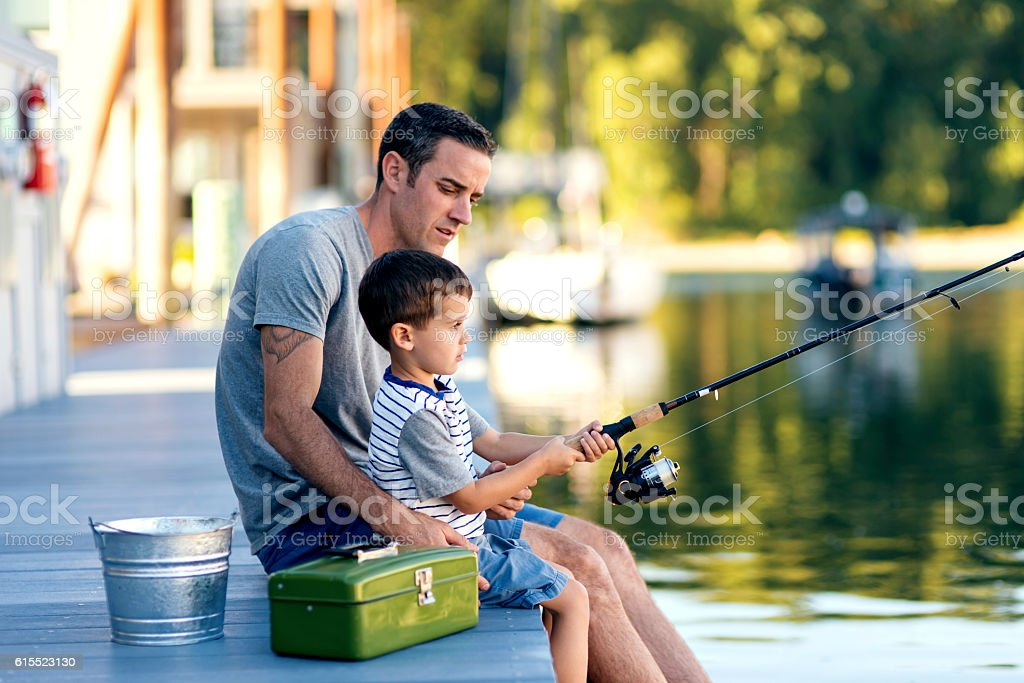 Father teaching son how to use a fishing pole stock photo
