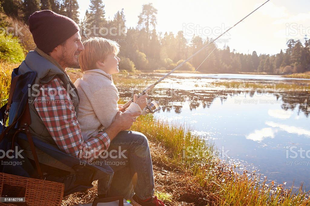 Father teaching son to fish sitting at lakeside stock photo