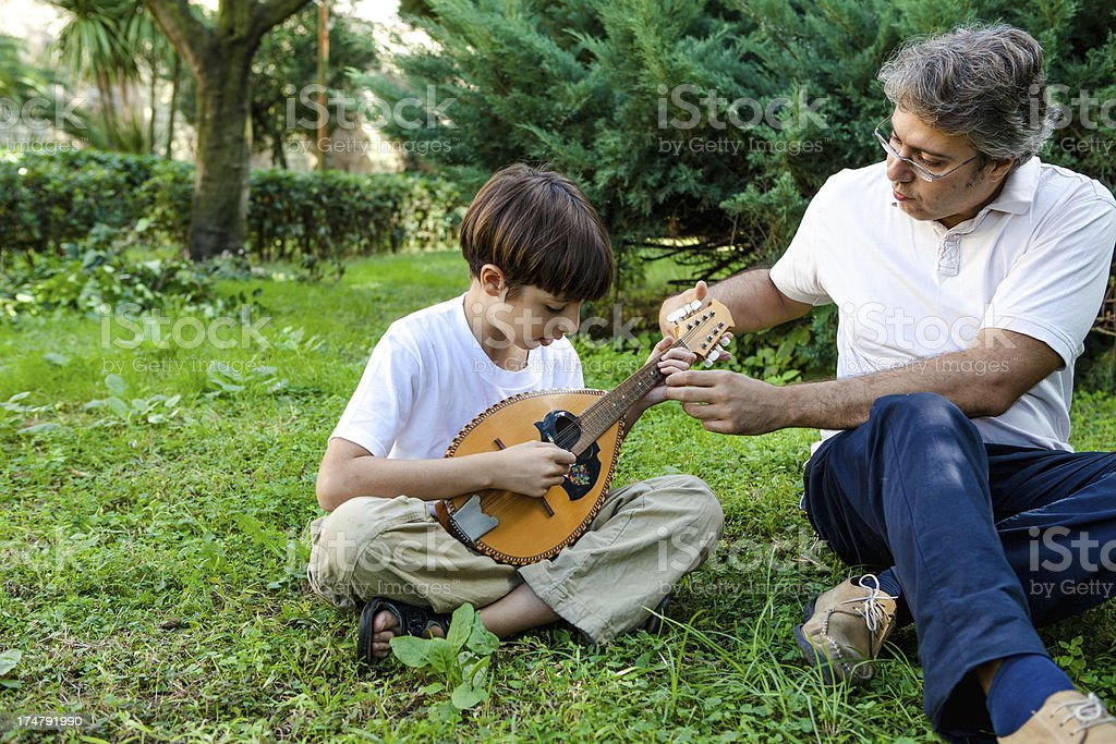 Father Teaching Son to Play Mandolin royalty-free stock photo