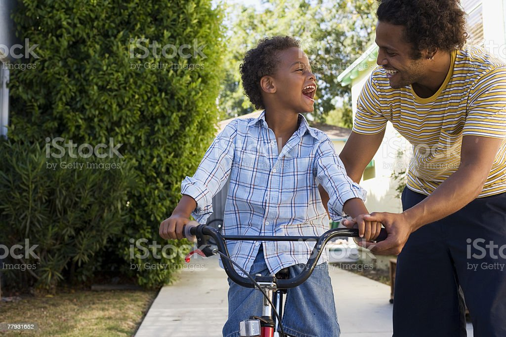 Father teaching son to ride bicycle in driveway stock photo