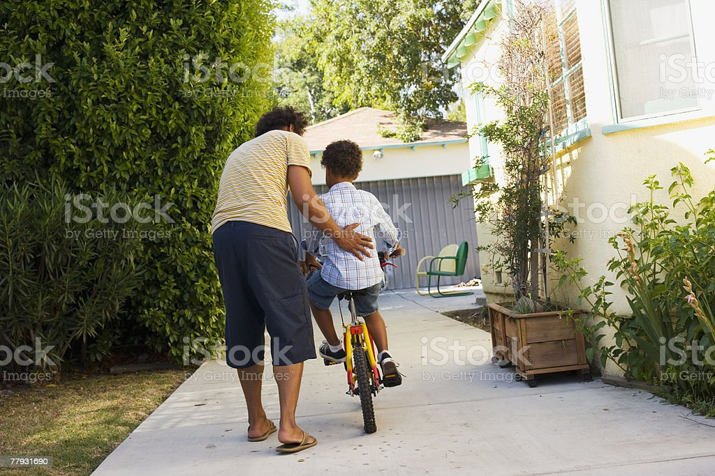 Father teaching son to ride bicycle in driveway royalty-free stock photo