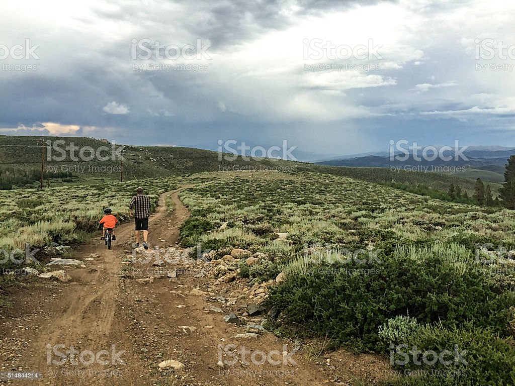 Father teaching son to ride bike on beautiful dirt road stock photo