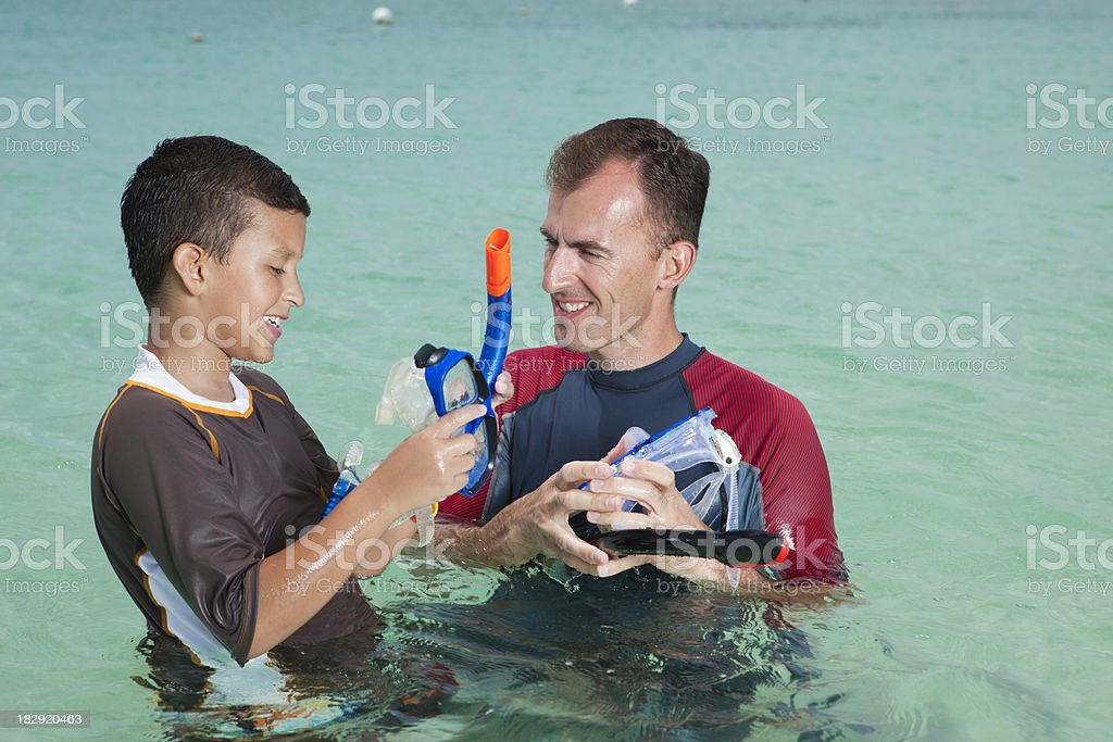 Father teaching son to snorkel royalty-free stock photo