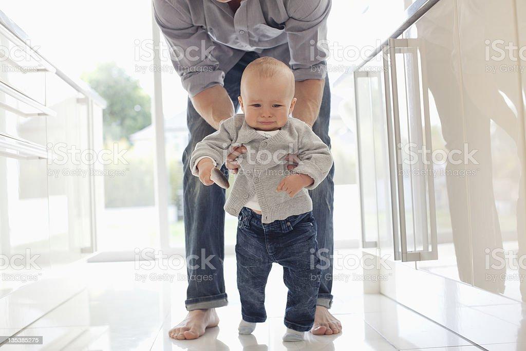 Father teaching son to walk royalty-free stock photo