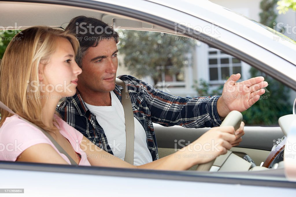 Father Teaching Teenage Daughter To Drive stock photo