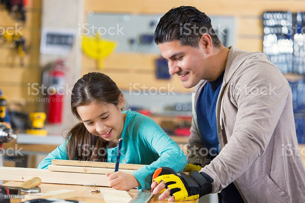 Father teaching young daughter to build something in workshop stock photo