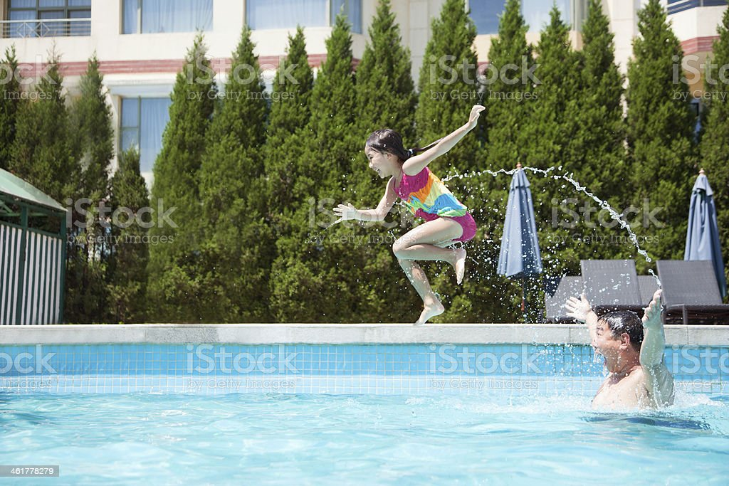 Father throwing daughter into the pool, mid-air stock photo