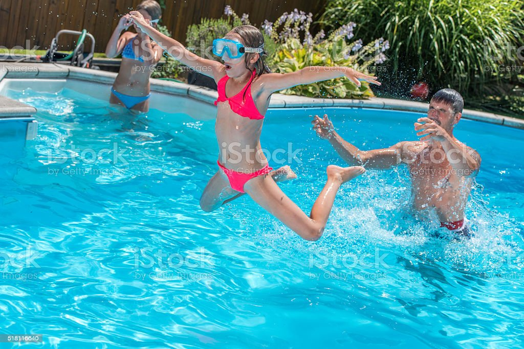 Father throwing his daughter in a pool stock photo