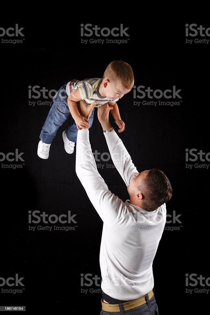 Father throwing his son in the air royalty-free stock photo