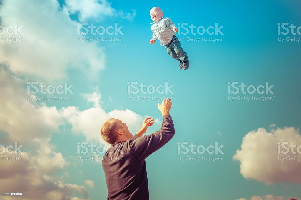 Father throwing son in air ready to catch him stock photo