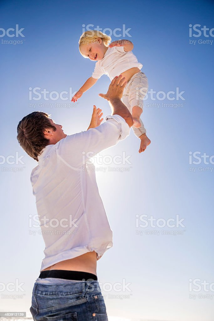 Father throwing son up and catching him stock photo