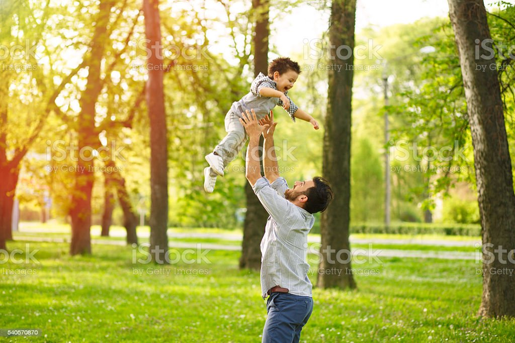 Father throwing up a happy boy in the air. stock photo