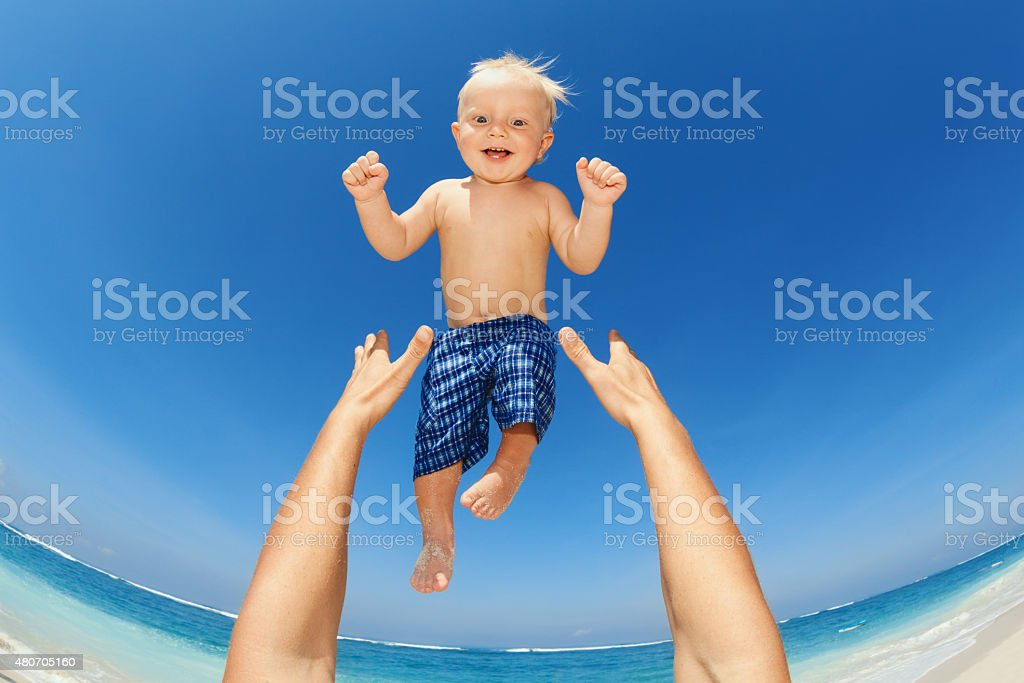 Father throwing up high in the air a happy child stock photo
