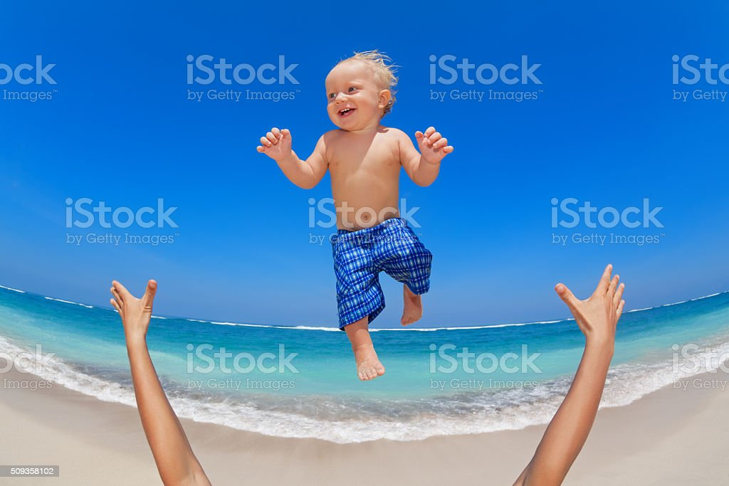 Father throwing up in the air a happy child stock photo