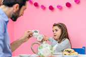 Father toasting his young daughter during their tea party
