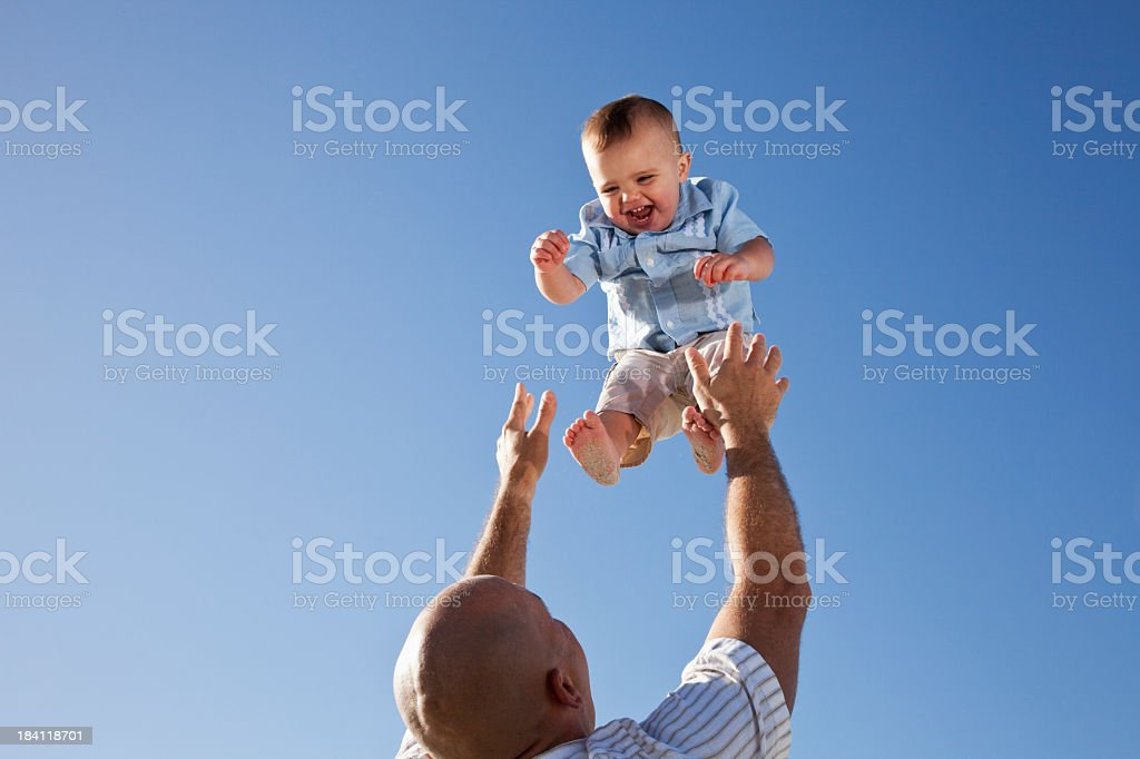 Father tossing little boy in air stock photo