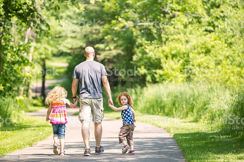 Father & Two Daughters Walking Through Wooded Park Trail stock photo