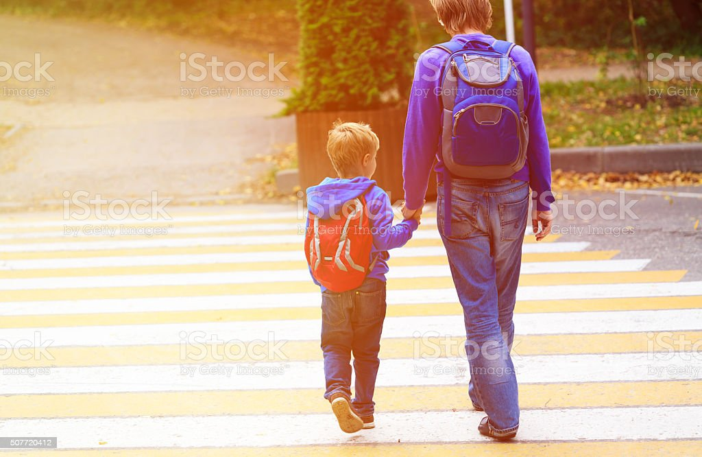 father walking little son to school or daycare stock photo
