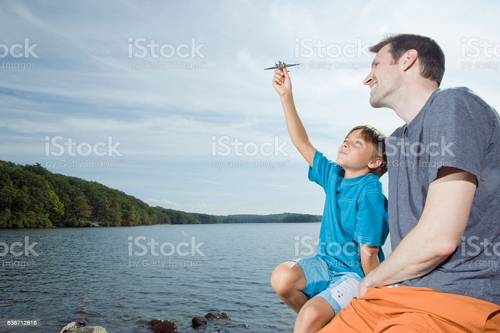 Father watching boy play with airplane next to lake stock photo
