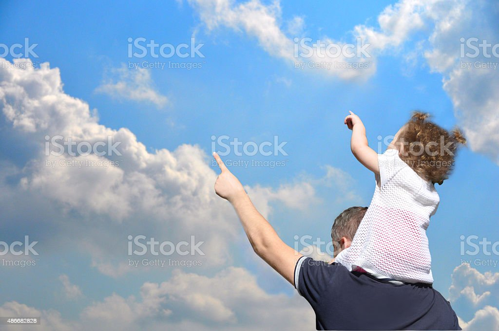Father with a baby show something against the sky stock photo