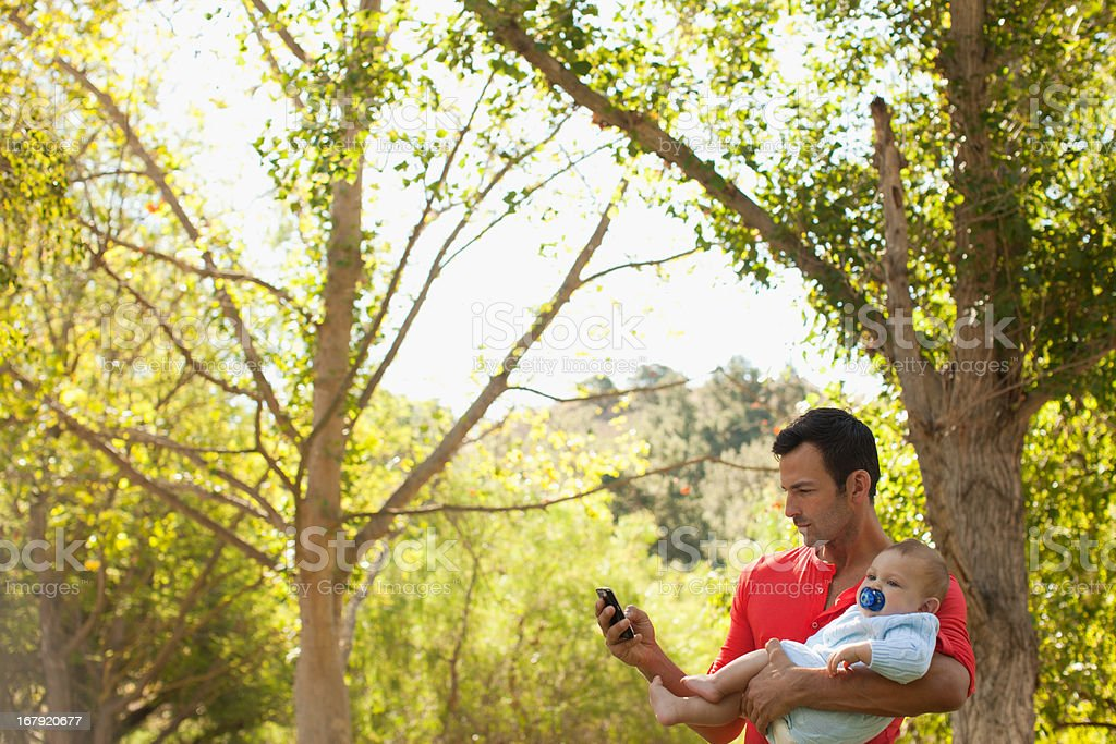 Father with baby using cell phone royalty-free stock photo