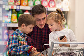 Father with children at supermarket