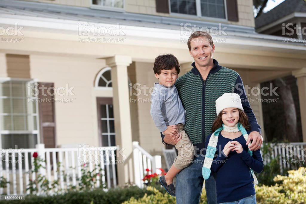 Father with children standing in front of house stock photo
