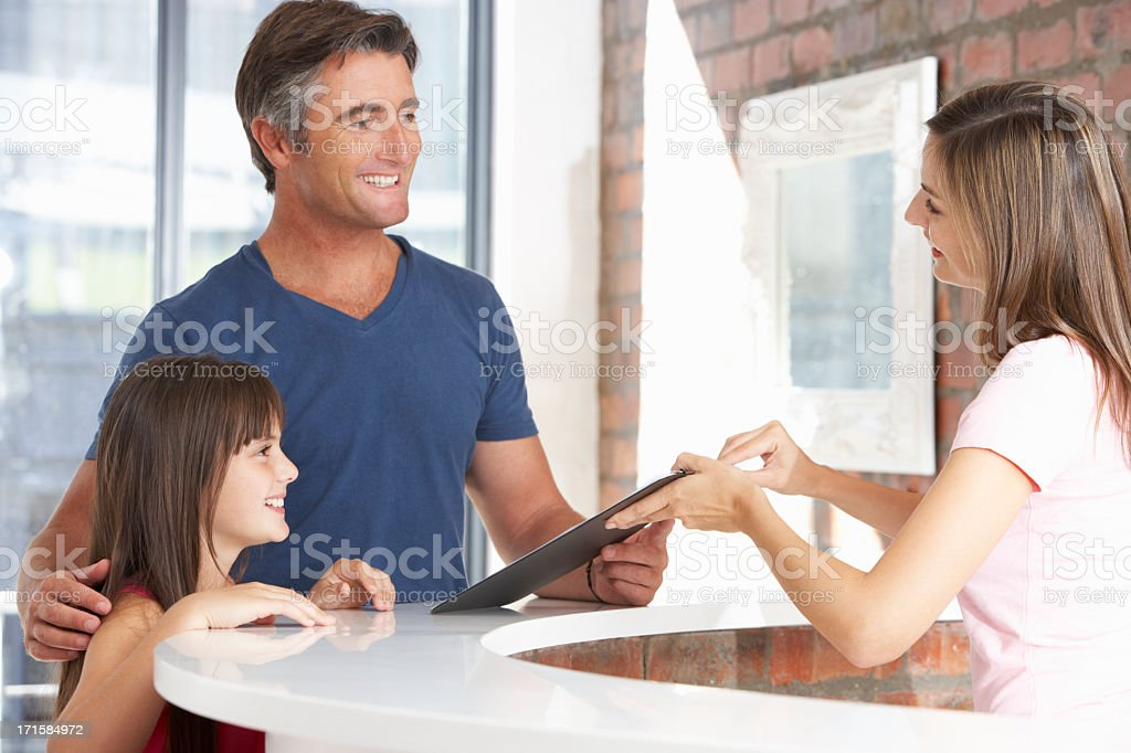 Father With Daughter At Reception Of Dentist's Surgery stock photo