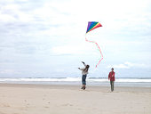 Father with daughter (8-9) flying kite on beach