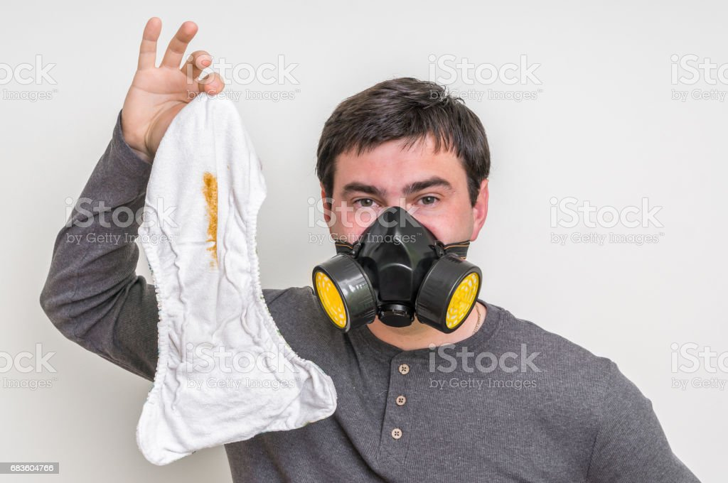 Father with gas mask changing smelly diaper stock photo