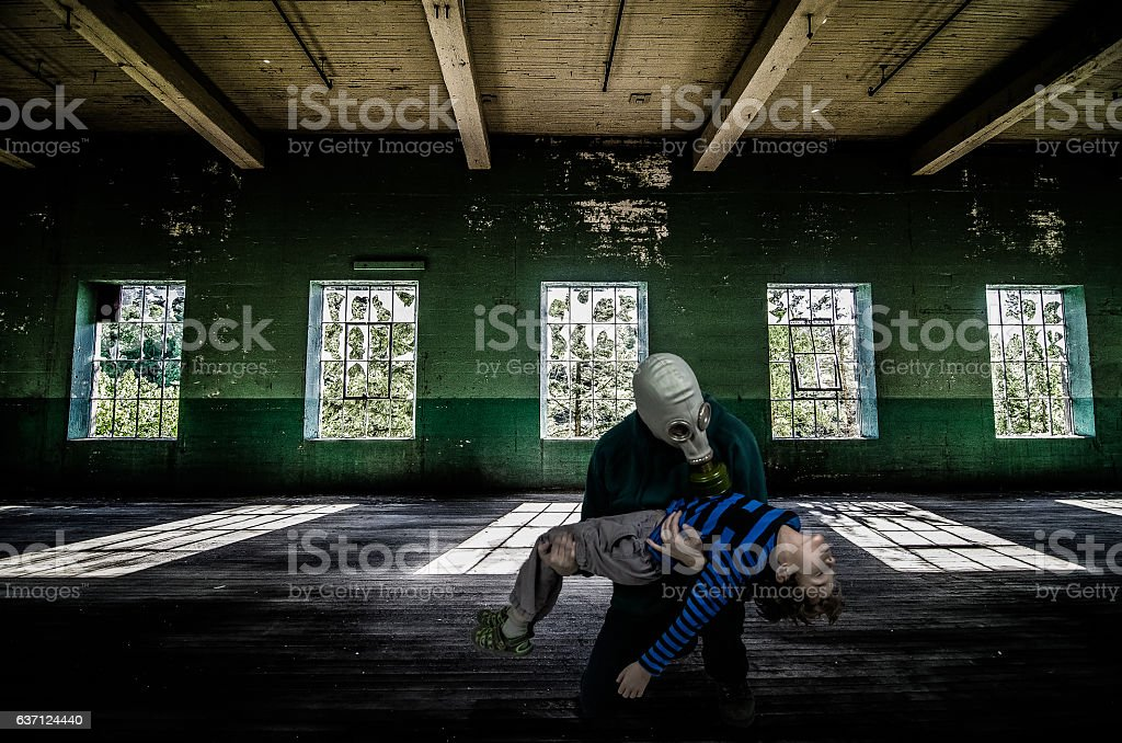 Father with gas mask holding dead son inside abandoned building stock photo