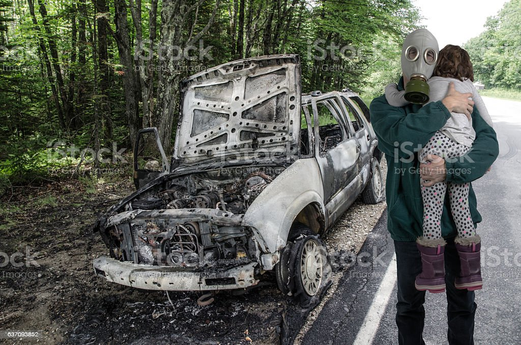 Father with gas mask holding her daughter besides burnt truck stock photo