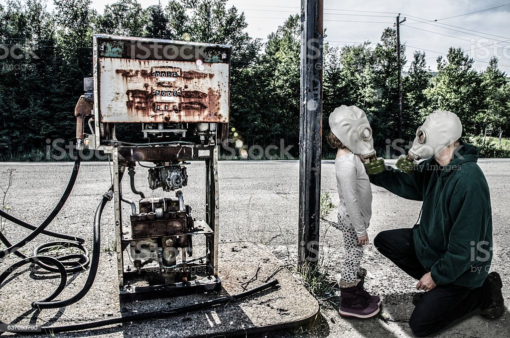 Father with gas mask placing mask on daughter stock photo